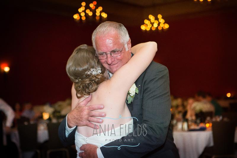 father hugging a bride